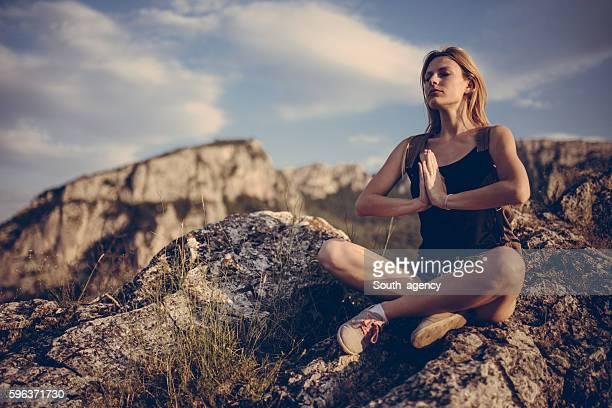 Female meditating on mountain