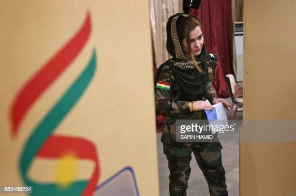 Female member of a Kurdish Peshmerga battalion casts her vote in the Kurdish independence referendum at a polling station in Arbil, on September 25,...