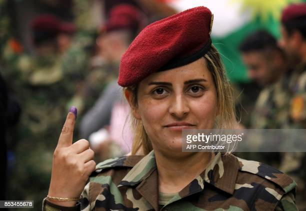 A female member of a Kurdish Peshmerga battalion shows her inkstained fingers after casting her vote in the Kurdish independence referendum in Arbil...