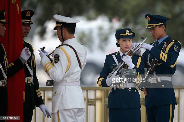 A female member of an honor guard prepares during a rehearsal before a welcome ceremony for German Chancellor Angela Merkel outside the Great Hall of...
