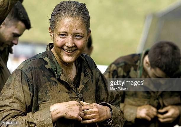 A female member of the US Naval Academy Freshman class takes off a wet jacket after wrestling in a mud pit during an event called Sea Trials at the...