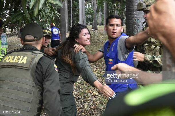 TOPSHOT A female member of Venezuela's Bolivarian National Armed Forces who deserted waves at a relative staying in Venezuela as she is being...