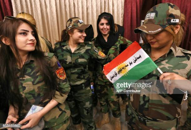 Female members of a Kurdish Peshmerga battalion queue inside a polling station as they wait to cast their vote in the Kurdish independence referendum...