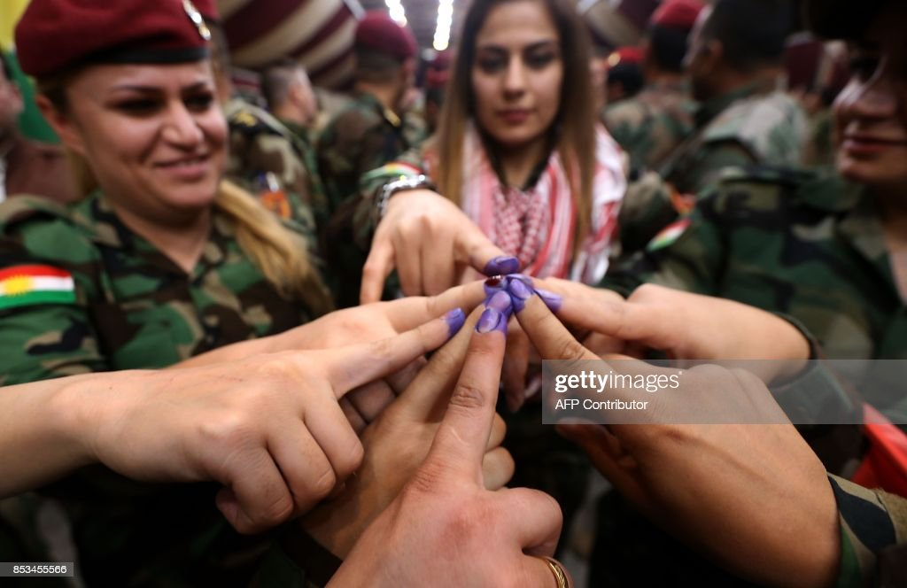 Female members of a Kurdish Peshmerga battalion show their ink-stained fingers after casting their vote in the Kurdish independence referendum in Arbil, on September 25, 2017. Iraqi Kurds voted in an independence referendum in defiance of Baghdad which has warned of 'measures' to defend Iraq's unity and threatened to deprive their region of lifeline oil revenues. /