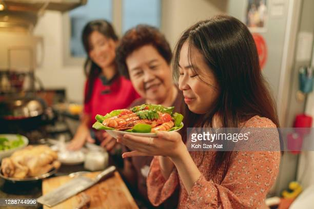 female members of a multi generation family during reunion dinner preparation for chinese new year - new generation stock pictures, royalty-free photos & images