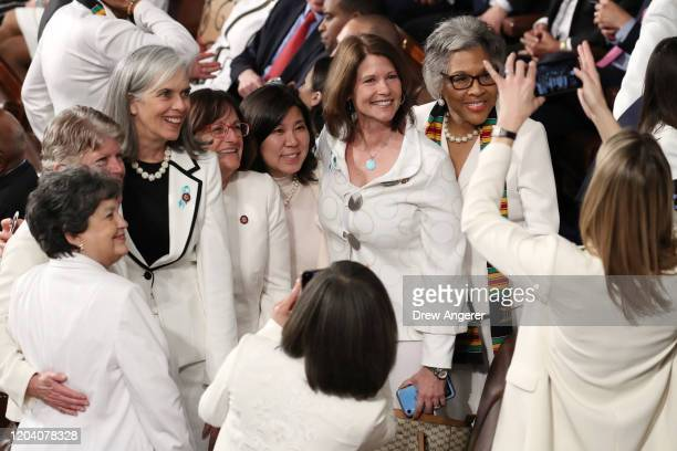Female members of Congress dressed in white pose for a photo ahead of the State of the Union address in the chamber of the U.S. House of...