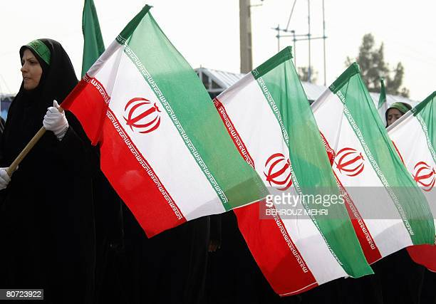 Female members of the Iranian Basij militia march past President Mahmoud Ahmadinejad as they hold their country's flag during the annual army day...