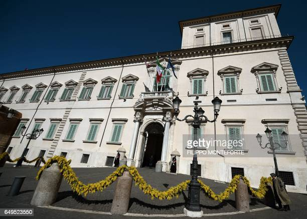Female members of the Italian Presidential Honor Guard stand at the entrance of the Quirinale Palace decorated with yellow mimosa on the occasion of...
