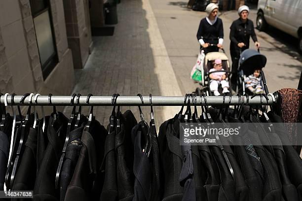 Female members of the Jewish Orthodox community walk by Orthodox mens jackets on a street in a Brooklyn neighborhood on June 14 2012 in New York City...