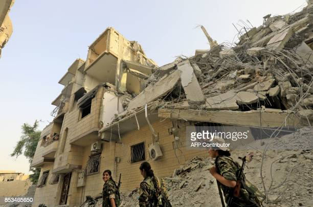Female members of the Syrian Democratic Forces walk through a damaged street in the former Islamic State stronghold of Raqa on September 22, 2017....