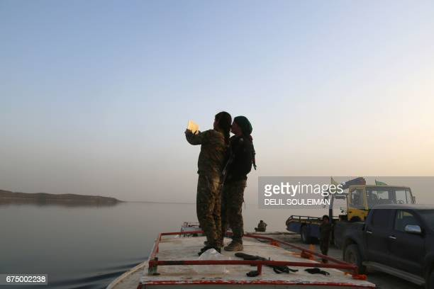 Female members of the USbacked Syrian Democratic Forces made up of an alliance of Arab and Kurdish fighters take a piture as they stand on a boat at...