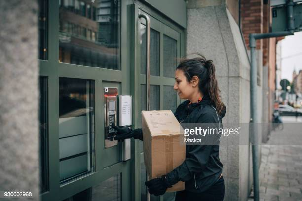 female messenger ringing intercom on closed door while carrying box on sidewalk - intercom stock photos and pictures