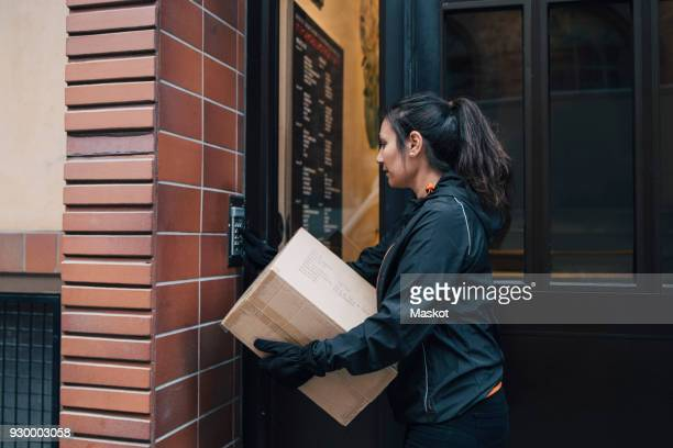 female messenger ringing intercom while carrying box by closed door - ringing doorbell stock pictures, royalty-free photos & images