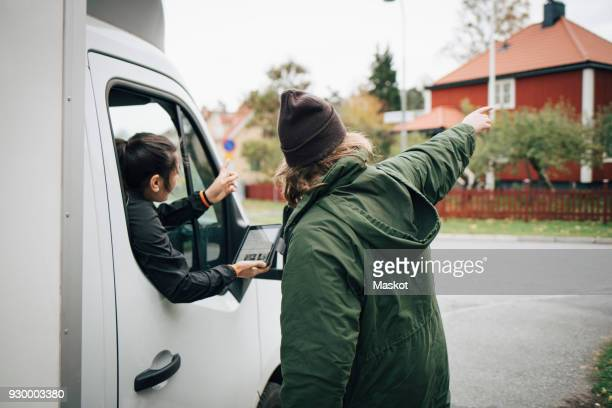 female messenger with digital tablet listening to man assisting during delivery - betrouwbaar stockfoto's en -beelden