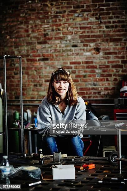 Female metal worker at workbench in metal workshop