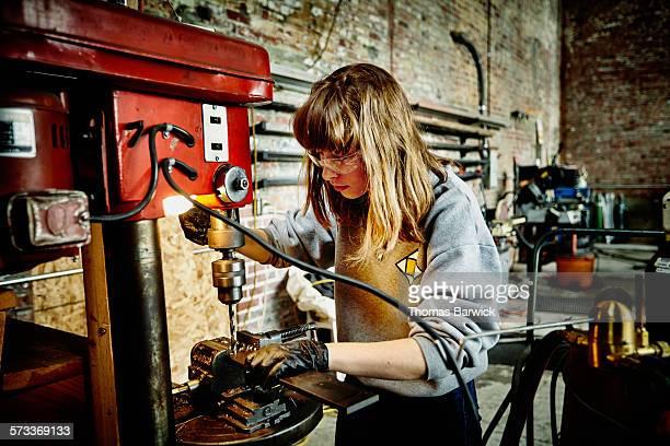 Female metal worker using drill press in workshop