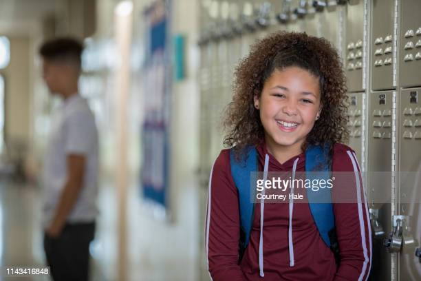 female middle school student smiling beside lockers - junior high student stock pictures, royalty-free photos & images