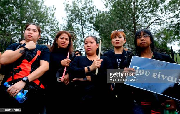 Female migrant workers hold candles and a banner reading Where are they as protesters demonstrate in support of the victims of a suspected serial...