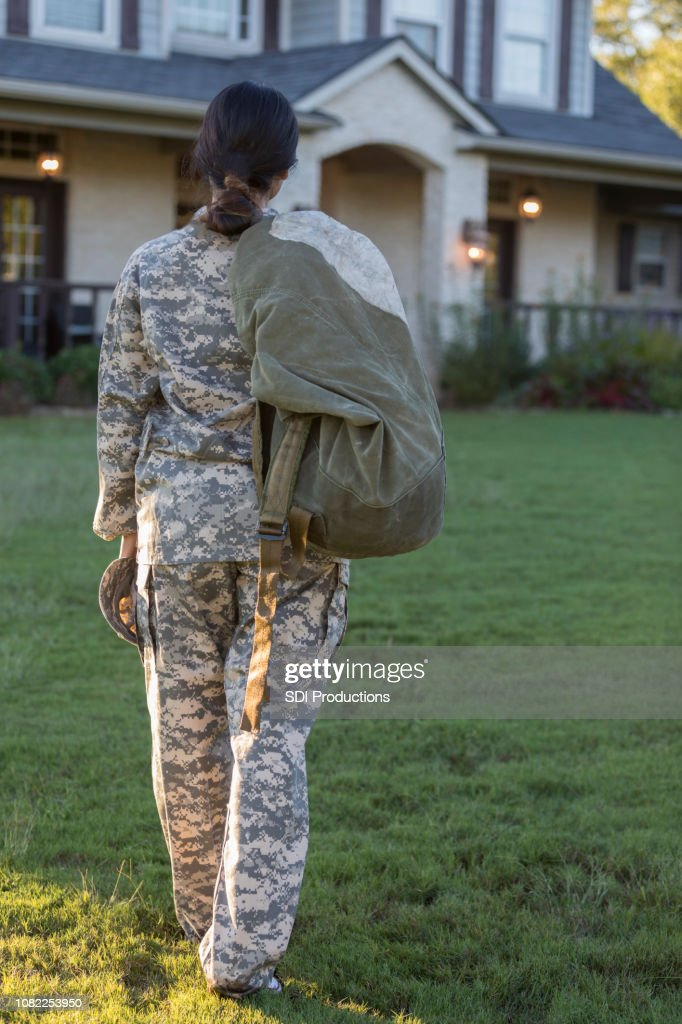 Female military officer looks longingly at house before tour of duty : Stock Photo