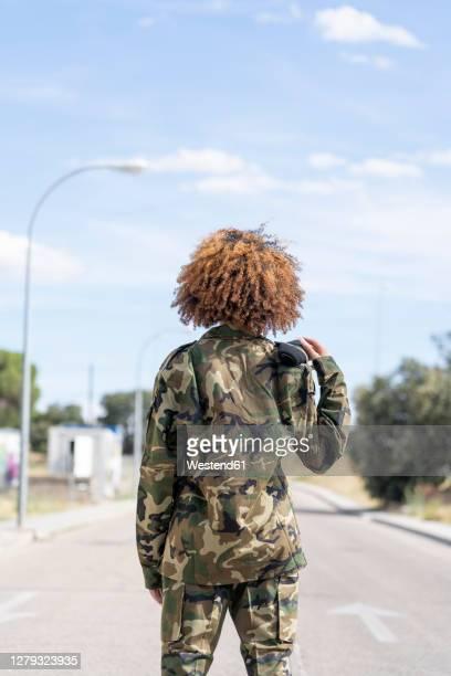 female military officer standing on street during sunny day - uniform stock-fotos und bilder