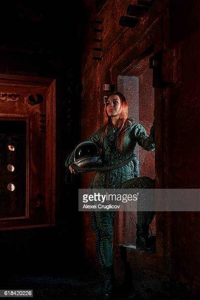 Female military pilot in bunker with helmet and flight costume