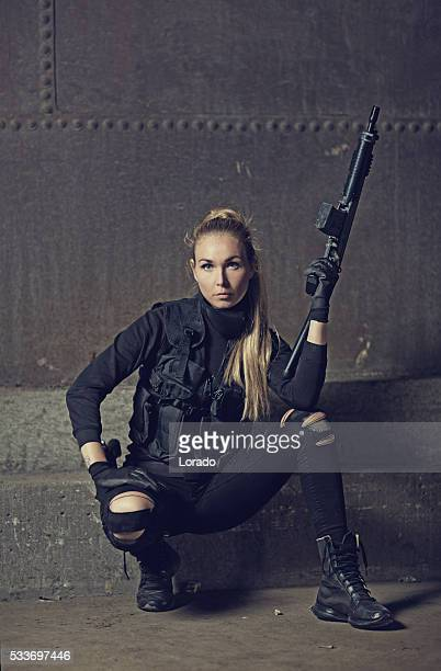 Female military swat team member holding rifle in abandoned warehouse