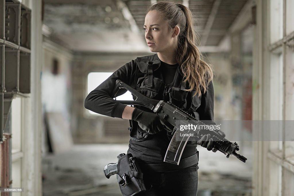 Militare femminile si consideri parte di un membro del team con fucile in magazzino abbandonato : Foto stock
