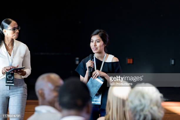 female millennial gives motivational speech to expo audience - panel discussion stock pictures, royalty-free photos & images