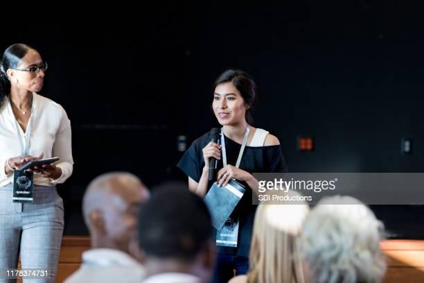 女性ミレニアル世代がエキスポの聴衆に意欲的なスピーチをする - パネル討論 ストックフォトと画像