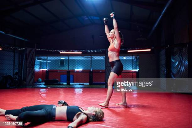 female mma fighters training in octagon. knock out - knockout stock pictures, royalty-free photos & images