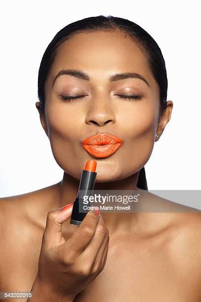 Female model applying orange lipstick