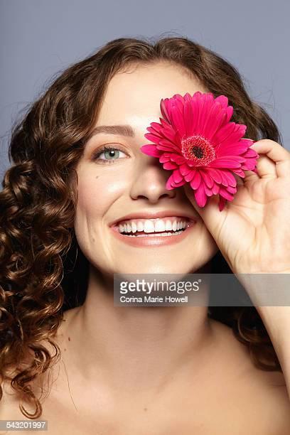 Female model covering eye with flower