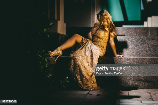female model in golden dress sitting on seat - gold dress stock pictures, royalty-free photos & images