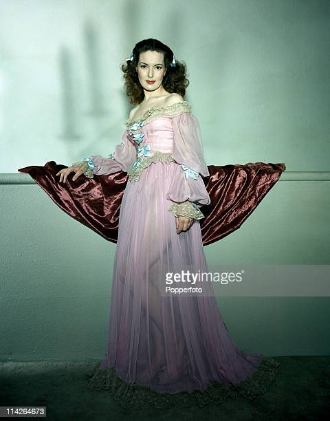 A female model leaning on a halfwall covered in a burgundy drape wears a sheer strapless pink negligee with fulllength flared skirt and puff sleeves...