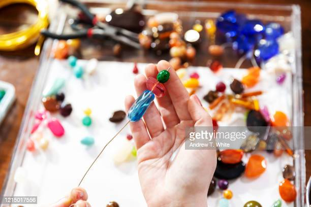 female model makes jewelry using beads, pliers and other tools at a workbench - bead stock pictures, royalty-free photos & images