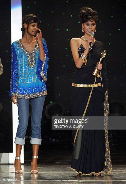 Female Model of the Year Ujwala Raul is awarded her trophy by presenter Liya during the 2004 Bollywood Fashion Awards at the Trump Taj Mahal 30 April...