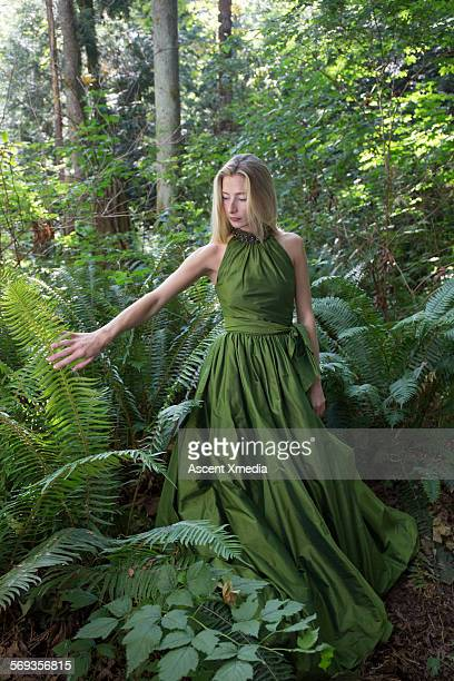 female model pauses in lush forest, contemplative - green dress stock pictures, royalty-free photos & images