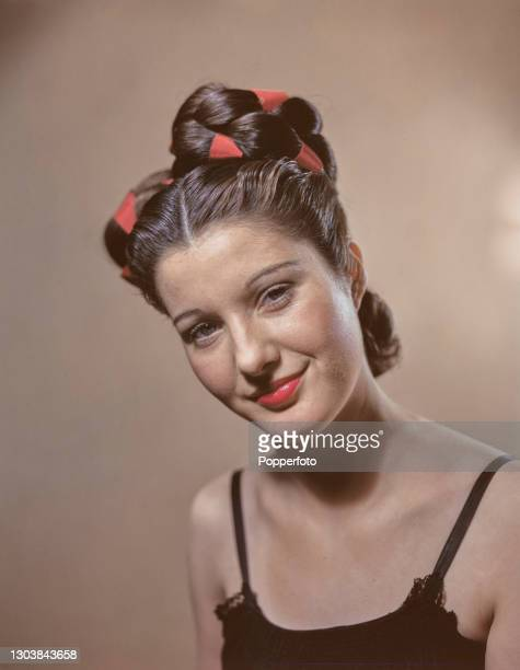 Female model poses with a Petersham Plait hairstyle, achieved with twin added plaits intertwined with scarlet ribbon and dressed in high coils either...