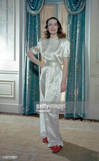 A female model posing in a white satin pyjamas ensemble with long trousers and a pleated top with short sleeves and wearing white red polkadot...