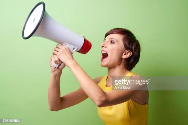 Female model shouting through megaphone. Debica, Poland