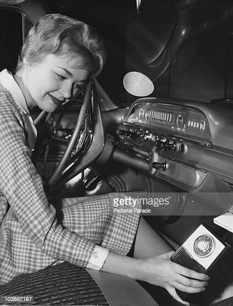 A female model sits at the steering wheel of a car operating a 'DoubleDuty' radio USA circa 1950 The 'DoubleDuty' radio was a new RCA transistor...