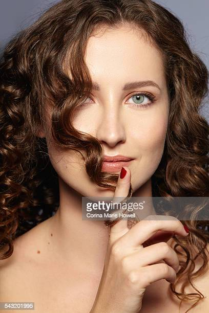 Female model twirling hair over face