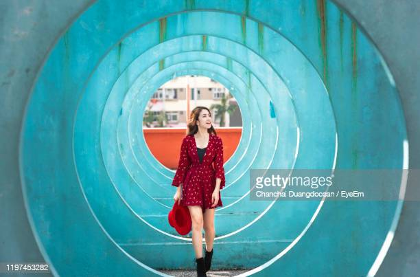 female model walking amidst turquoise circular structures - people stock pictures, royalty-free photos & images