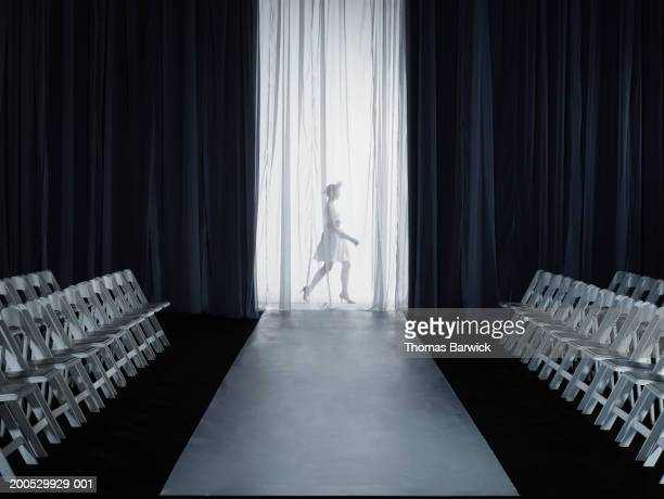 female model (15-17) walking backstage at fashion show, side view - catwalk stock pictures, royalty-free photos & images
