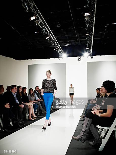 Female model walking down catwalk at fashion show