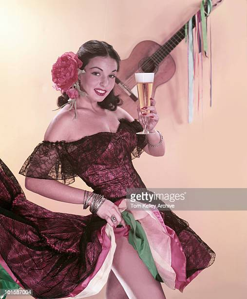 A female model wearing a red Spanish dress with a large red rose in her hair raises a glass of beer in greeting 1958 She pulls up her skirt...