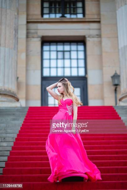 female model wearing pink evening gown while standing on steps - red carpet event stock-fotos und bilder