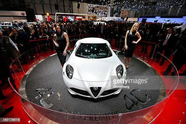Female models help launch the new Alfa Romeo 4C automobile produced by Fiat SpA on the first day of the 83rd Geneva International Motor Show in...