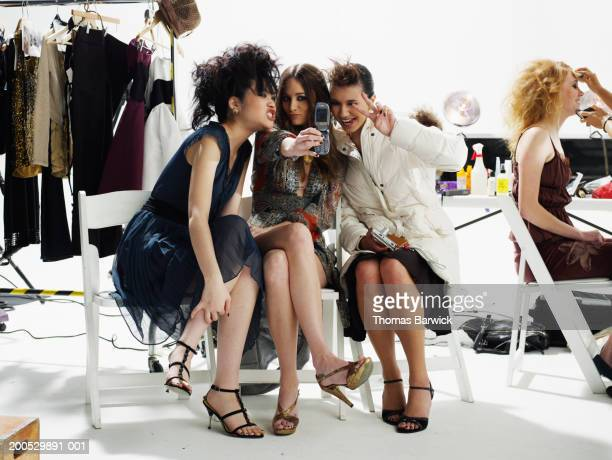 Female models photographing themselves with camera phone