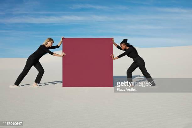 female models pushing maroon portal on white sand at desert - diverbio foto e immagini stock